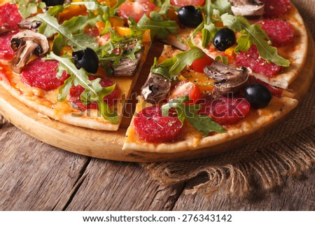 Pizza with rucola, salami and olives close-up on the table. horizontal, rustic style  - stock photo