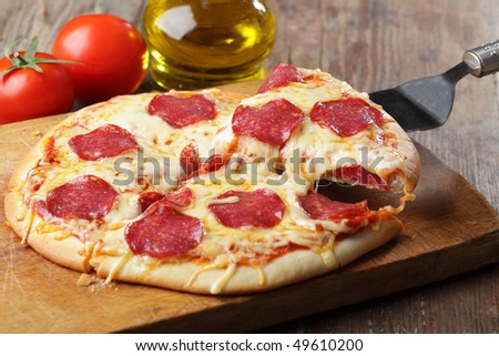 Pizza with salami and cheese on a cutting board - stock photo