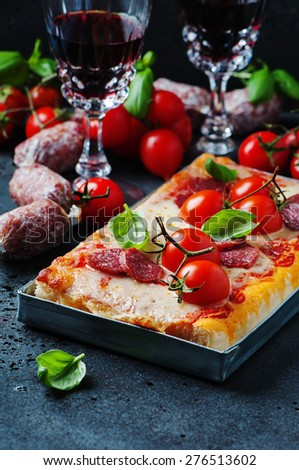 Pizza with salami and tomato, selective focus - stock photo