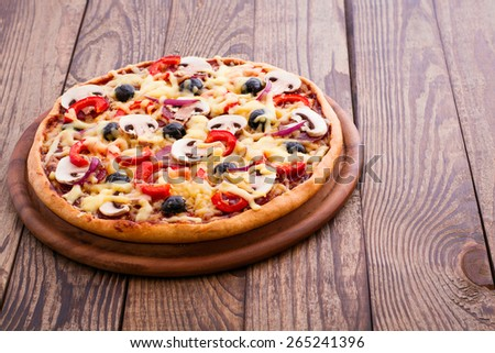 Pizza with salami, mushrooms, mozzarella and basil on wood table horizontal