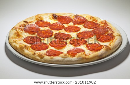Pizza with sausages served on white plate.  - stock photo