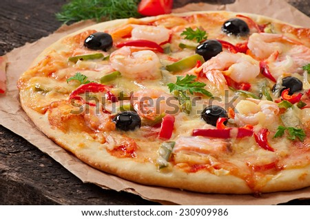 Pizza with shrimp, salmon and olives - stock photo