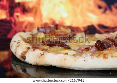 Pizza with smoked streaky bacon, pineapple, ham and pepperoni by clay oven, macro with copy space - stock photo
