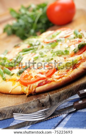 Pizza with tomato and string bean on the cutting board - stock photo