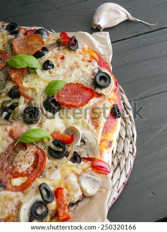 pizza with tomatoes, mushrooms, olives and peppers served on a wooden table