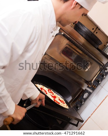 Pizzeria worker with baked Italian pizza posing near oven