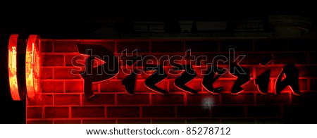 pizzerias red lighted adverdising words on the wall - stock photo