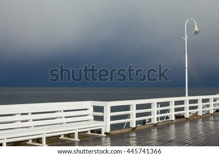 Place for meditation concept. Beautiful view from white wooden pier to calm sea and rainbow. Cloudy weather. Copy-space. Outdoor shot