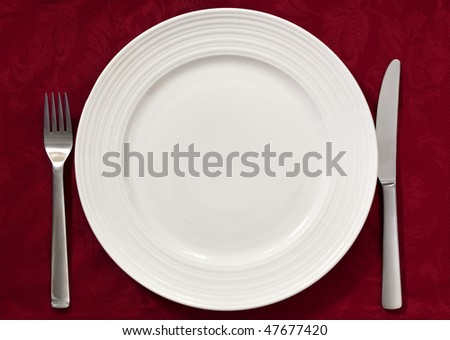 Place setting on red damask tablecloth.  Silverware and dinner plate.