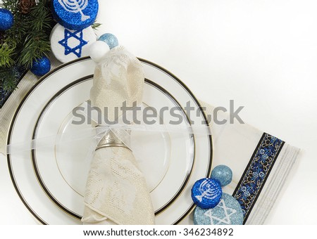 Place setting using white china dishes with black and gold trim topped with a sparkly napkin in a silver ring tied with a white bow. Evergreen and blue and white decorations for Hanukkah. Copyspace - stock photo