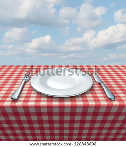 Place setting with a fork knife and white empty plate on a checkered red and white tablecloth on a summer blue sky as a food service and classic restaurant symbol and picnic dining. - stock photo