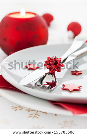place setting with candle and cutlery  - stock photo