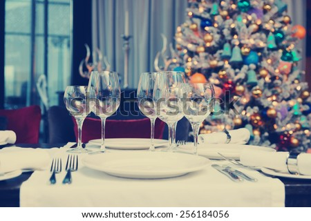 Place setting with Christmas tree in background, toned image - stock photo