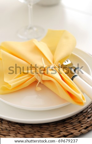 place setting with yellow napkin - stock photo