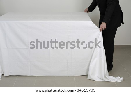 Placing a tablecloth on a buffet table - stock photo