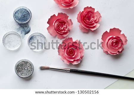 Placing glitter on the pink paper flowers - stock photo