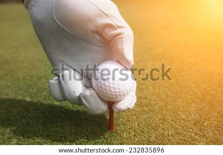 Placing golf ball on a tee - stock photo