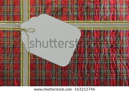 Plaid gift wrapped package with large blank gift tag - stock photo