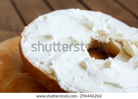 Plain bagel cut in half and spread with cream cheese, detail on wood. - stock photo