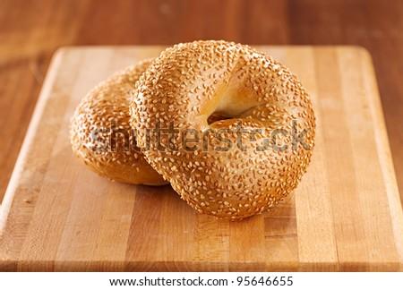 plain bagel on wooden board. - stock photo