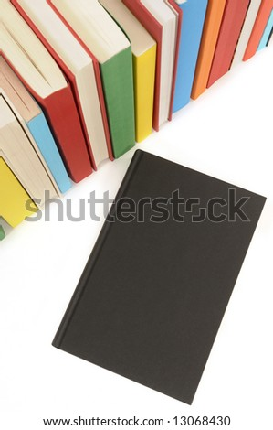 Plain black book with row of colorful books isolated on a white background.  Space for copy. - stock photo