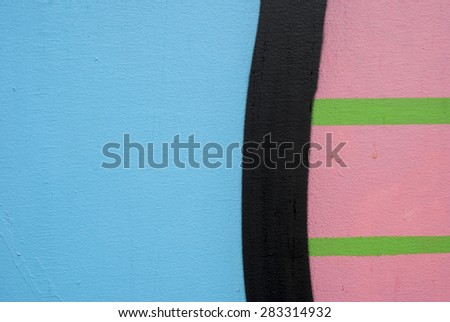 Plain blue and black, green, pink stripes on wall. - stock photo