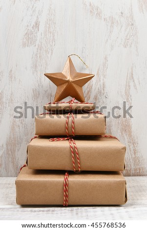 Plain brown paper wrapped gifts tied with twine and stacked in the shape of a Christmas tree with star, against rustic white wood background.