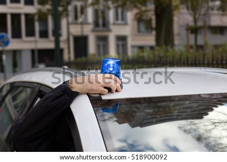 plain clothes officer mounting rotating emergency light on a car