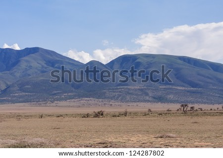 Plain savanna grass field against mountain and cloudy sky background. Serengeti National Park, Tanzania, Africa.