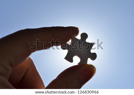 Plain white jigsaw puzzle on Background of blue sky and sun. - stock photo