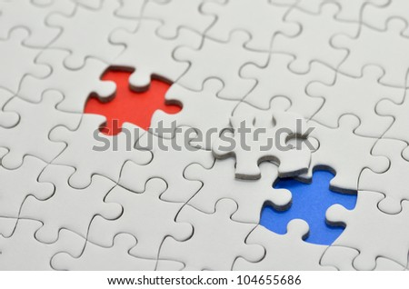 Plain white jigsaw puzzle, on Blue Red background.