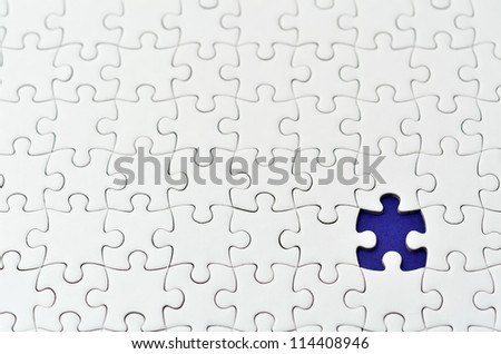 Plain white jigsaw puzzle, on Navy background. - stock photo