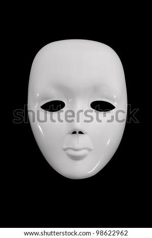 Plain white mask against a dark background. - stock photo