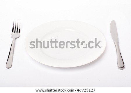 Plain white plate with knife and fork, with soft shadow