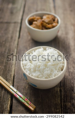 plain white rice bowl on brown rustic background, Low Key Lighting Technique, Shallow DOF - stock photo