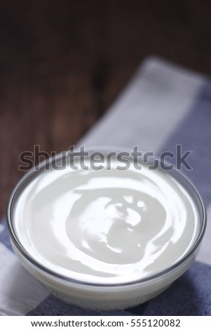 plain yogurt in small glass bowl on cotton cloth place on old wood background. white yoghurt. plain yogurt. yoghurt.