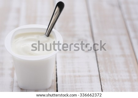 plain yogurt in white plastic cup on wooden white background. white yoghurt. plain yogurt. yoghurt.