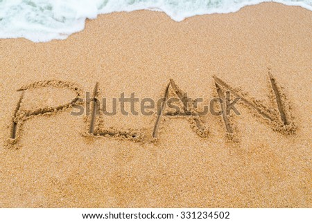 PLAN inscription written on sandy beach with wave approaching. - stock photo