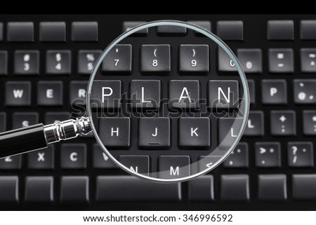 PLAN written on keyboard with magnifying glass