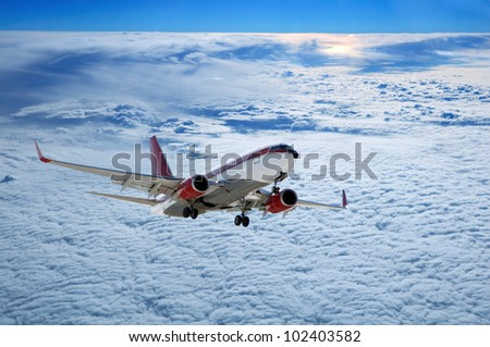 plane above Cute cloudscape with sunset - stock photo