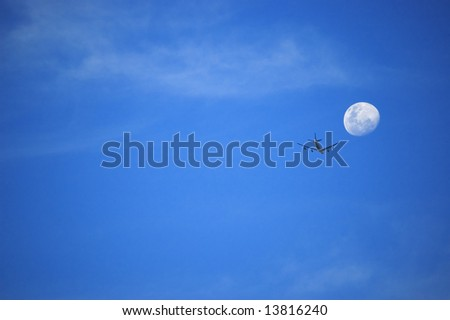 Plane and moon against blue sky. - stock photo
