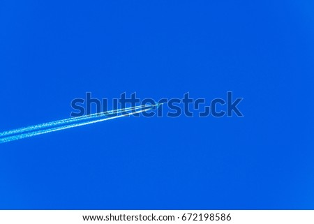 Plane at cruising altitude, airplane with chemtrails on blue sky, sunny day