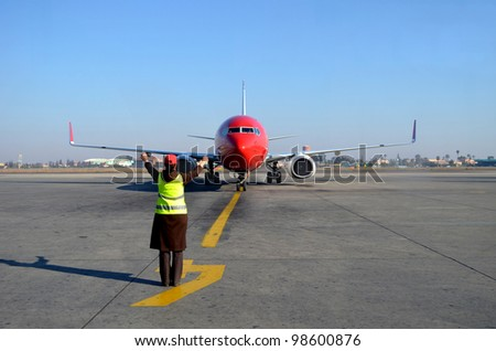 Plane being signaled by woman at airport - stock photo