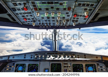 plane cockpit and cloudy sky - stock photo