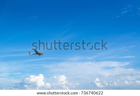 Plane flies in blue sky against the background of clouds