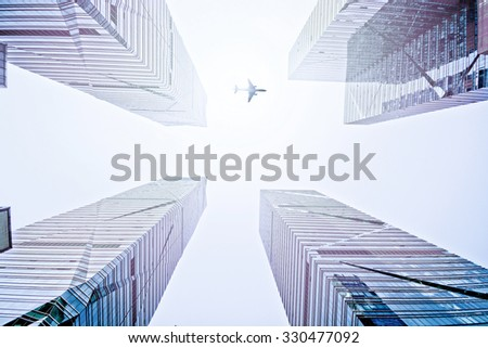 plane fly above the modern city - stock photo