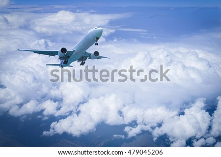 Plane flying above cloud with blue sky background.