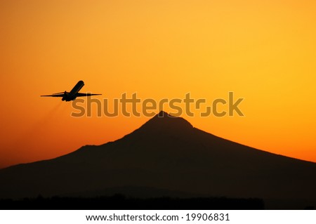 Plane flying into sunrise over Mt. Hood, Oregon USA - stock photo