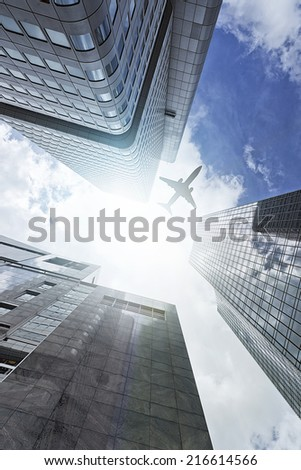 plane flying over a modern glass and steeel office towers in Frankfurt am Main, Germany - stock photo