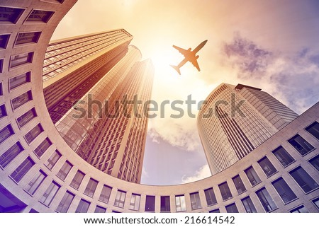 plane flying over modern office tower in the sun, Frankfurt am Main, Germany - stock photo